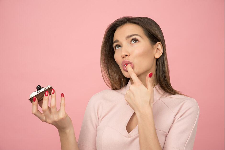 食べかけのカップケーキを持ちながら、指先を舐めている女性