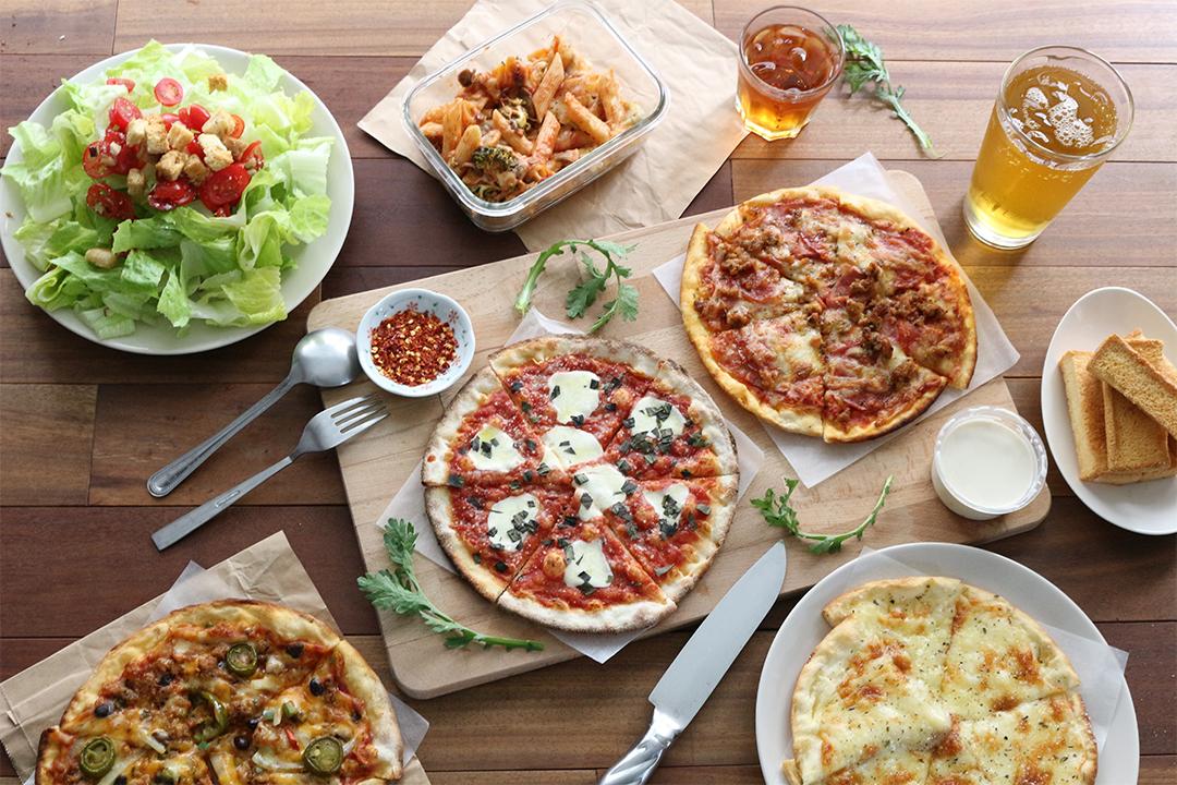 テーブルに並んだピザ、ドリンク、サラダ