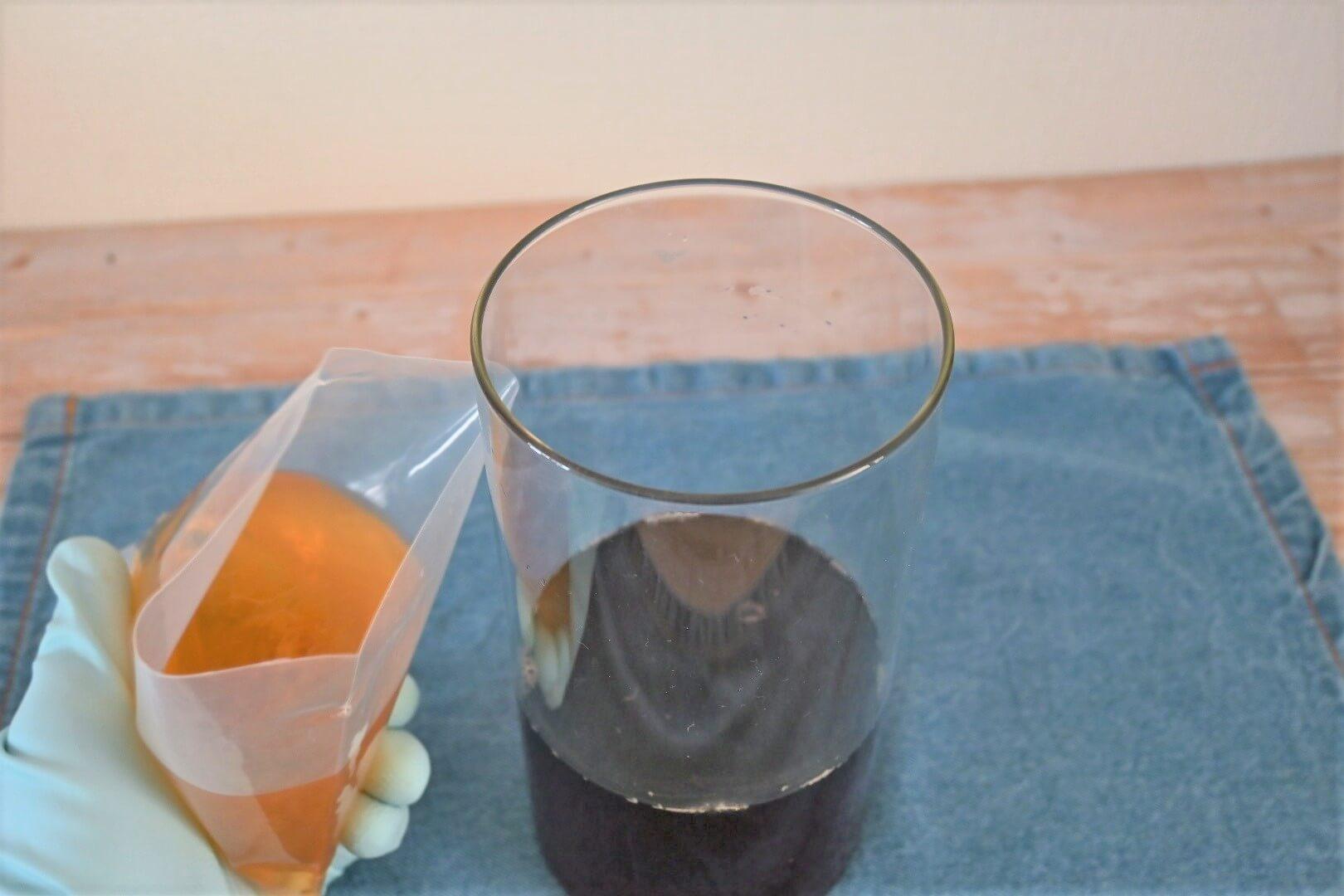 紅茶が入った瓶と種菌を持った手
